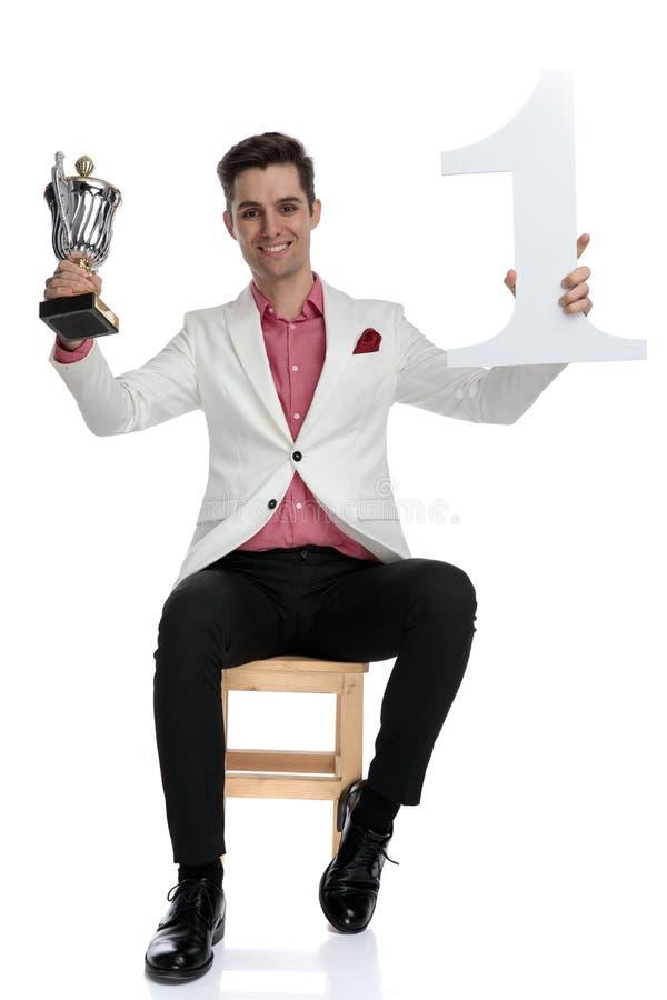Troféu elgant bem sucedido novo da terra arrendada do homem de negócios e número um acima foto de stock