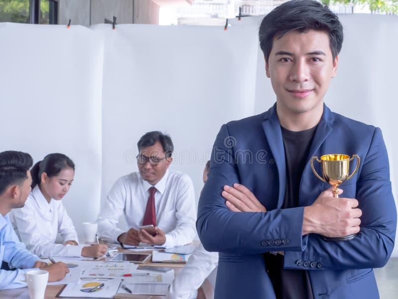 Trofeo e sorridere della tenuta dell'uomo d'affari Collega dell'uomo dell'uomo d'affari ad una riunione fotografia stock