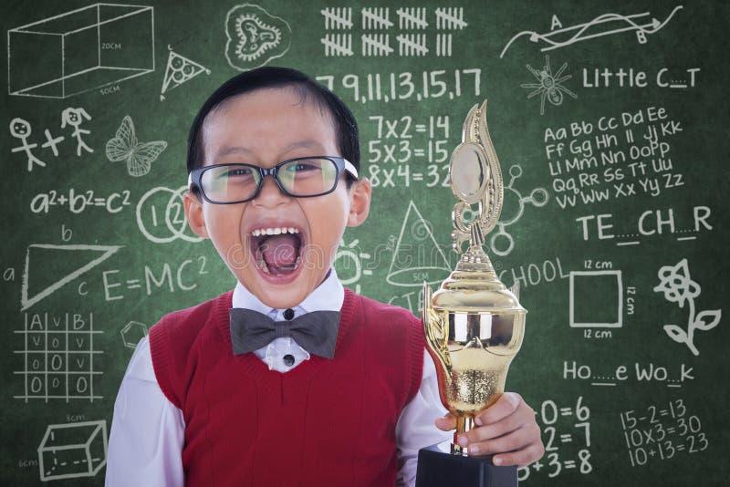 Trofeo emozionante della tenuta del ragazzo dello studente nella classe fotografia stock libera da diritti