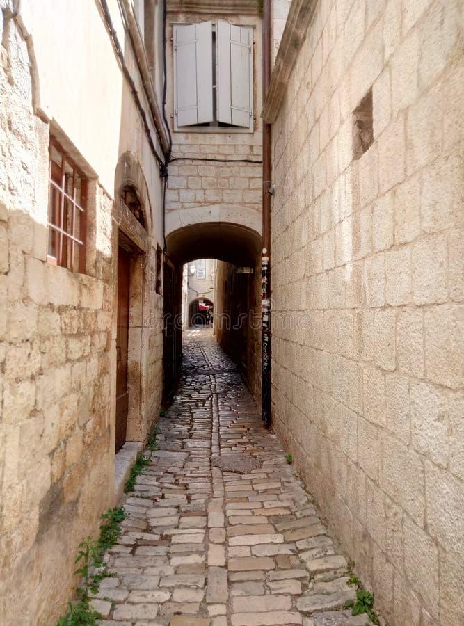 Trogir/Kroatien - 26. Juni 2017: Schmale Straße im Stadtzentrum von Trogir Der Weg von pawing Steinen lizenzfreie stockbilder