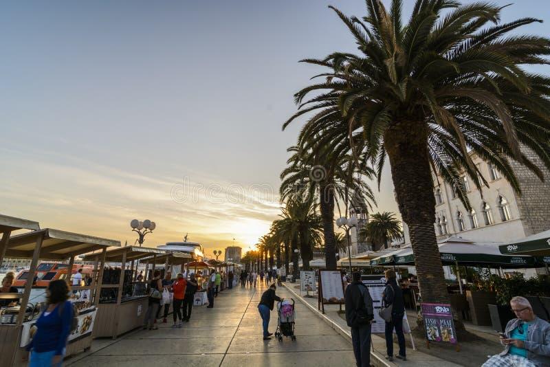 TROGIR KROATIEN, OKTOBER 01 2017: Turister som går gods för en köpande till köpmannen på den centrala gatan på solnedgången royaltyfria bilder