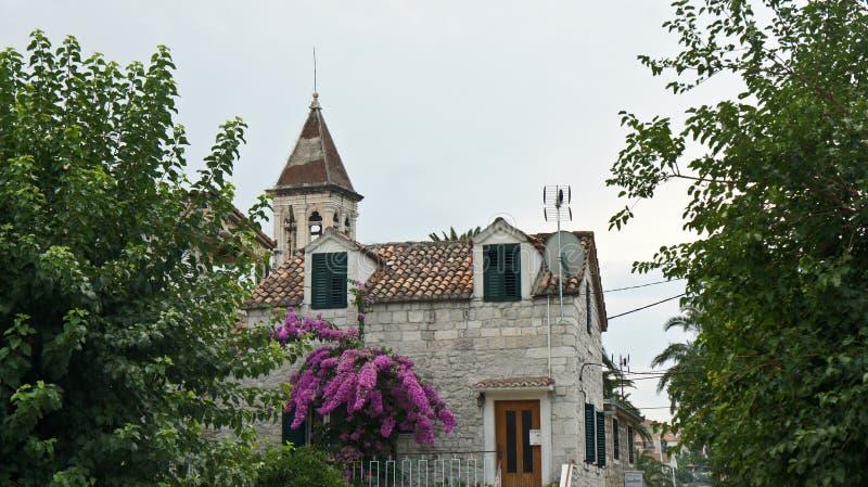 Trogir Kroatien - 07 25 2015 - stenhus i gatan av den gamla staden, härlig arkitektur med träd, torn av kyrkan av arkivfoto