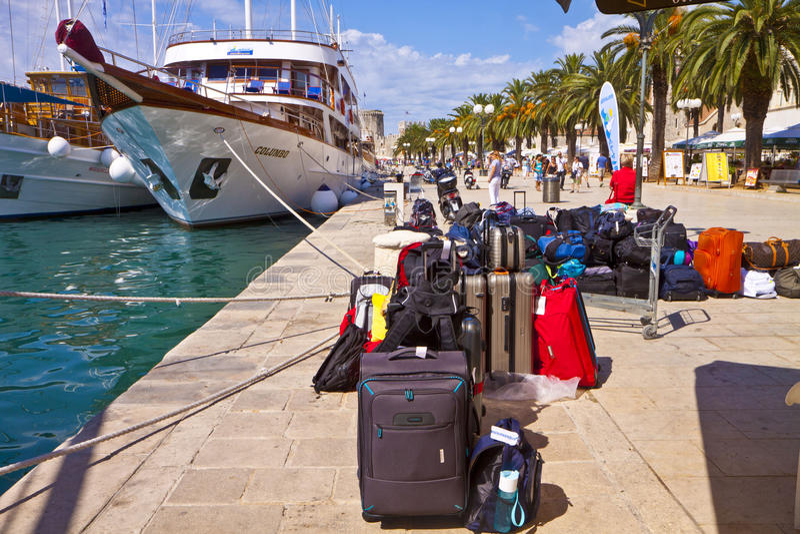 Trogir Kroatien - Touristic kryssningskepp och passagerarebaggagesnolla arkivbilder