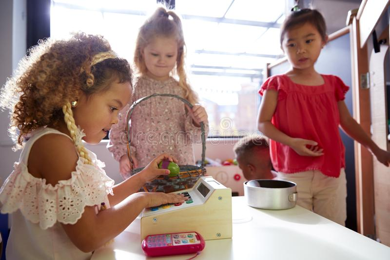 Trois écolières de jardin d'enfants jouant le magasin dans une maison de théâtre à une école infantile, éclairée à contre-jour images libres de droits