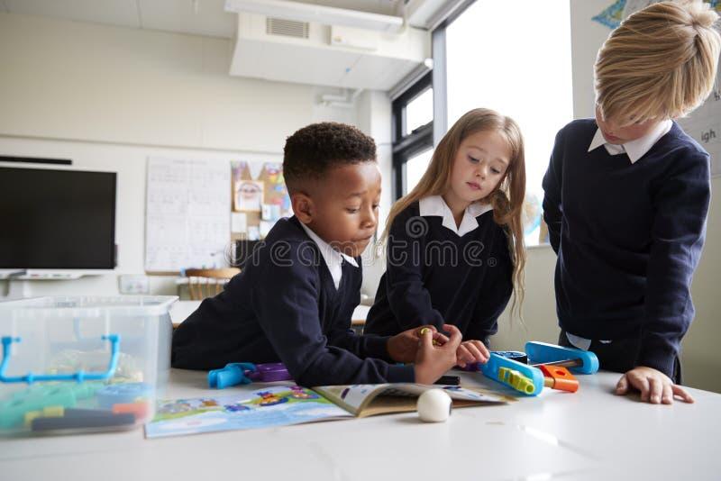 Trois écoliers primaires se tenant à une table dans une salle de classe collaborant avec des blocs de construction de jouet, fin, photo stock