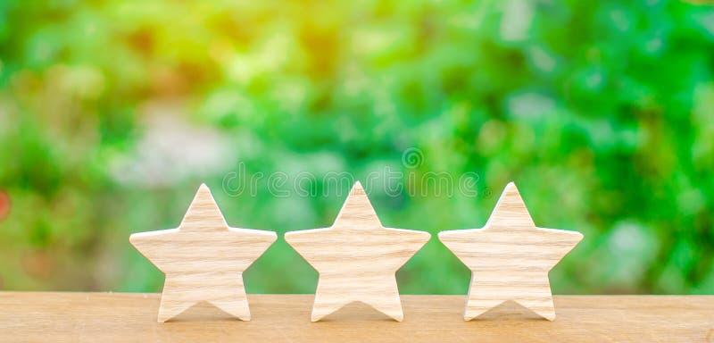 Trois étoiles en bois L'estimation de l'hôtel, restaurant, application mobile Le concept de l'estimation et de l'évaluation Servi photos stock