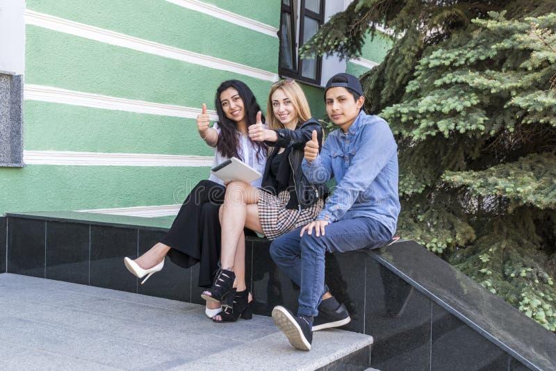 Trois étudiants avec des pouces  photographie stock