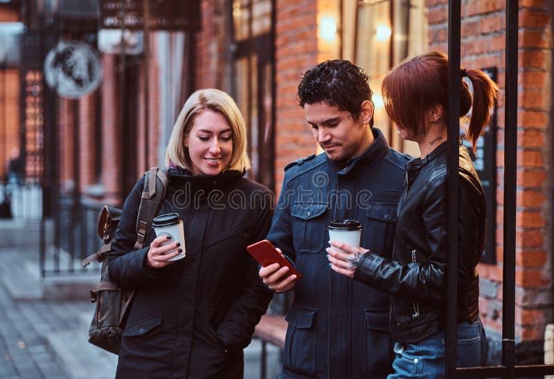 Trois étudiants d'amis ayant une coupure avec du café près d'un café dehors images libres de droits