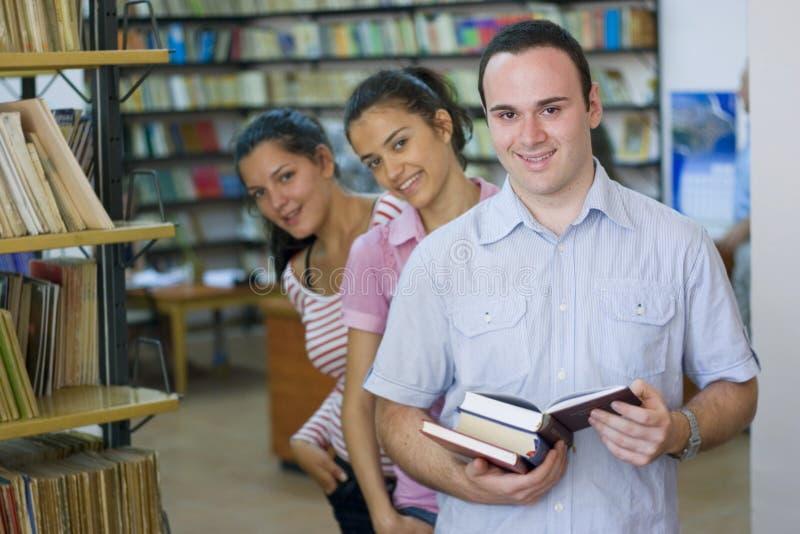 Trois étudiants dans la bibliothèque image stock