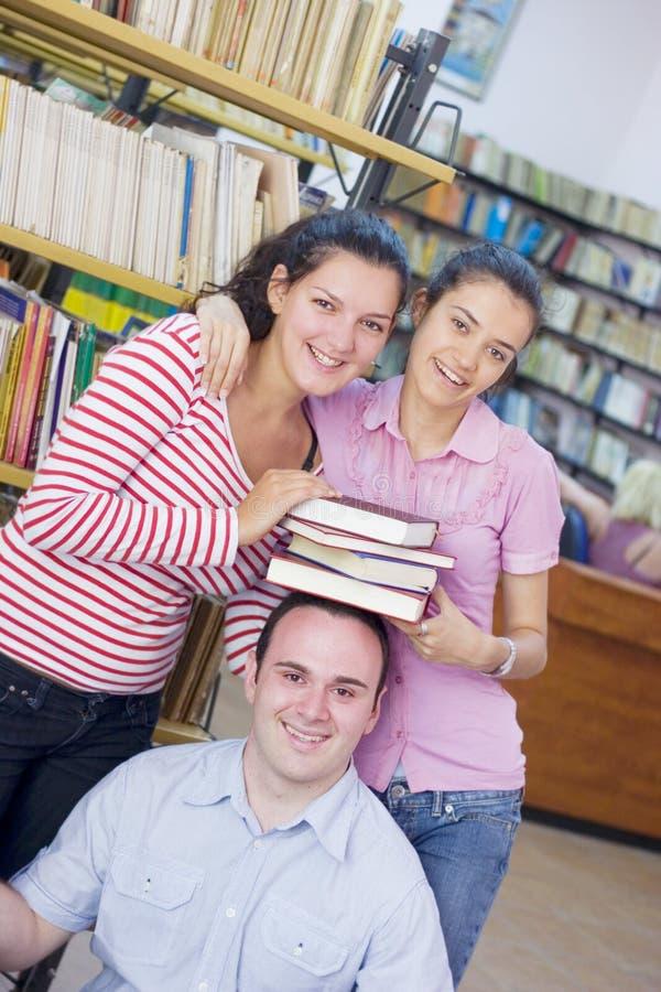 Trois étudiants dans la bibliothèque images stock