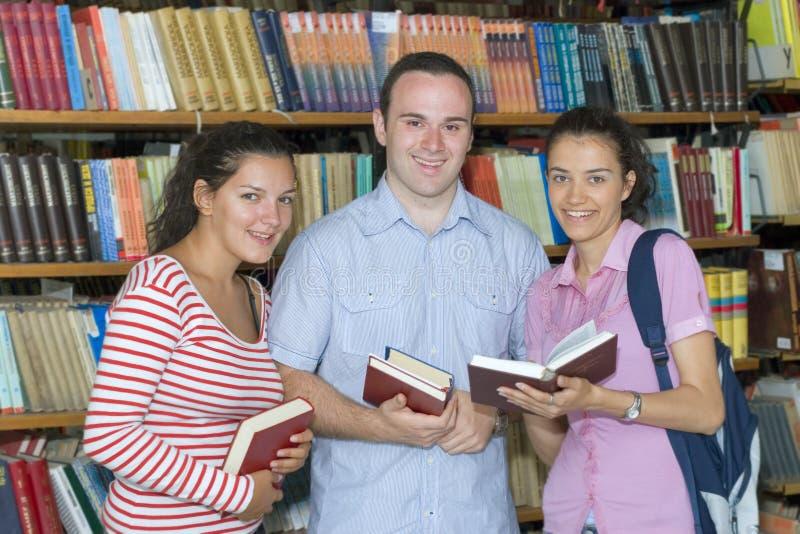Trois étudiants dans la bibliothèque photo libre de droits