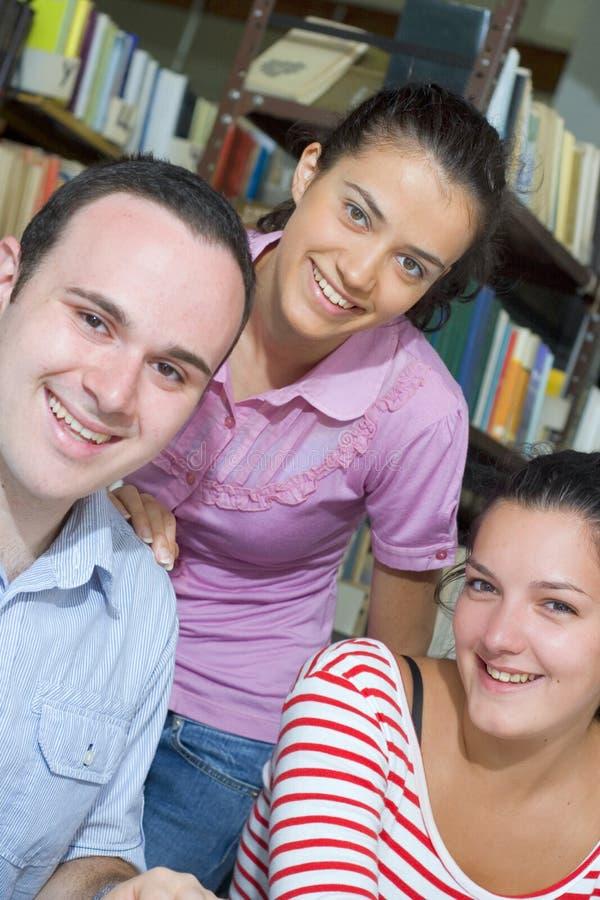 Trois étudiants dans la bibliothèque photos libres de droits