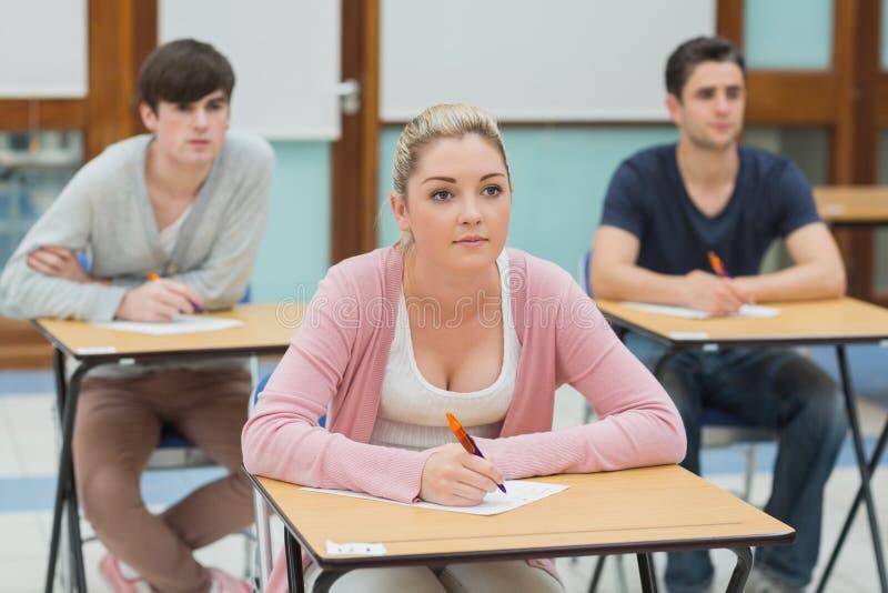 Trois étudiants dans une salle de classe environ pour prendre des notes photographie stock