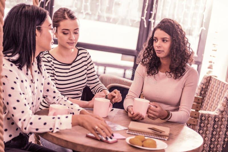 Trois étudiants principaux dépensant leur coupure dans le cafétéria confortable près de l'université images stock