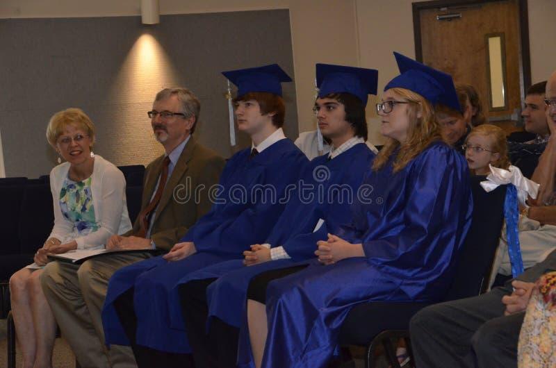 Trois étudiants reçoivent un diplôme de l'école à la maison photo libre de droits
