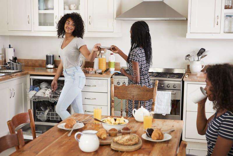 Trois adolescentes dégageant le Tableau après petit déjeuner de famille image libre de droits