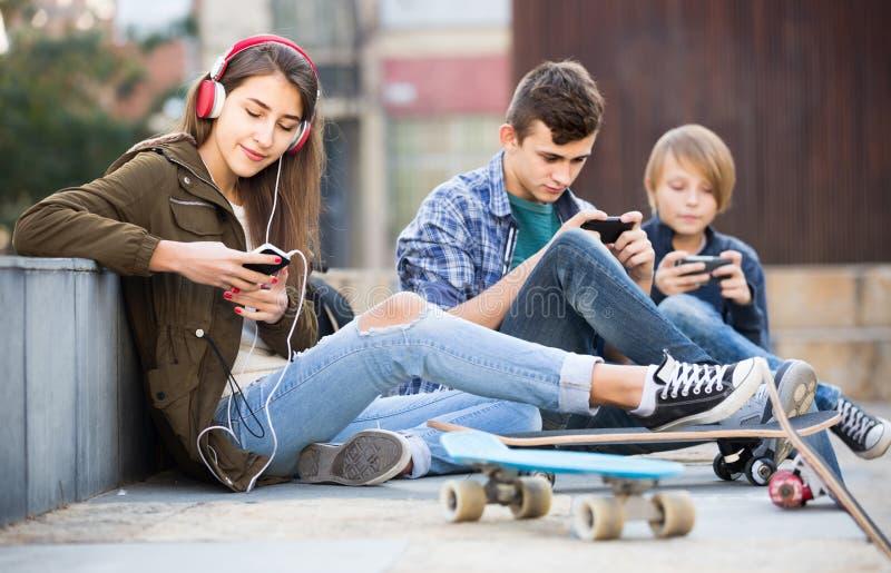 Trois adolescents avec des smartphones dedans dehors images stock
