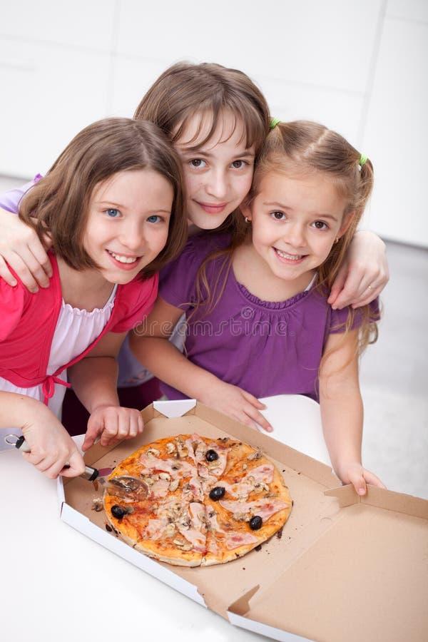Trois amies partageant une pizza photo stock