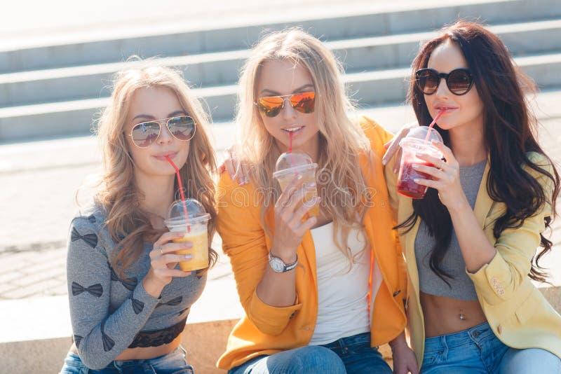 Trois amies s'asseyant sur des étapes en parc photos stock