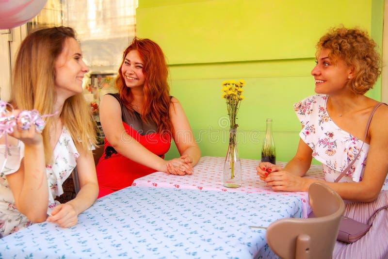 Trois amies s'asseyent dans un café sur la rue et le sourire photo libre de droits