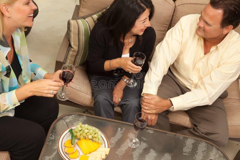 Trois amis appréciant le vin sur le patio photos stock