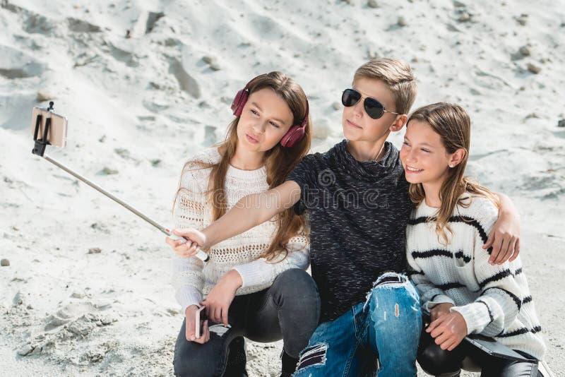 Trois amis avec un selphie de makind de samoyed de race de doog sur une plage photos stock
