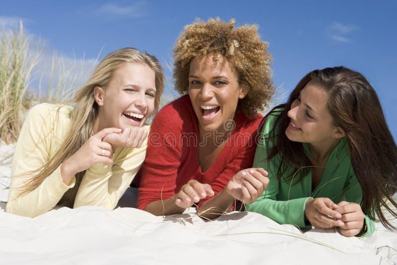 Trois amis ayant l'amusement à la plage photographie stock libre de droits