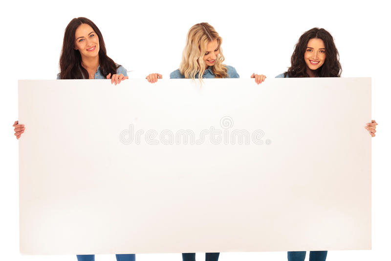 Trois amis de femmes tenant un panneau d'affichage et un sourire vides photo stock