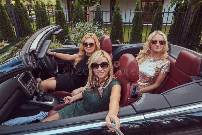Trois amis féminins à la mode heureux prennent une photo de selfie dans la voiture de luxe de cabriolet, pendant leurs vacances d image libre de droits