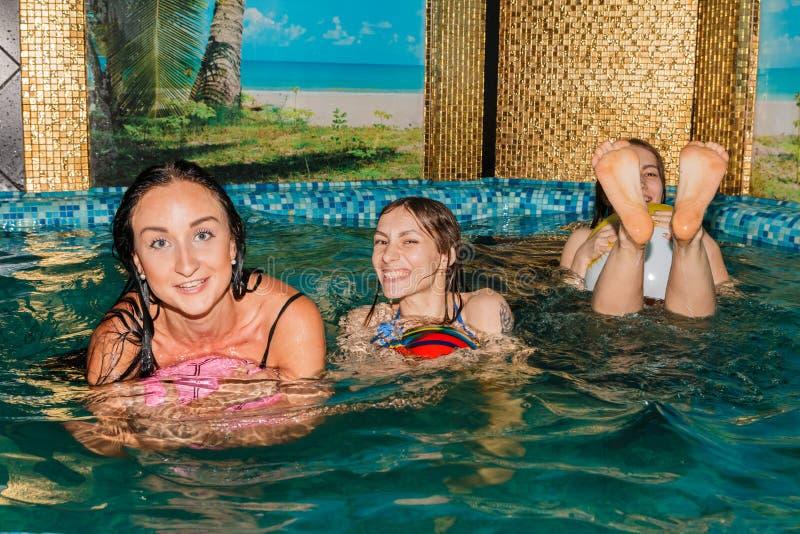 Trois amis féminins en piscine photographie stock
