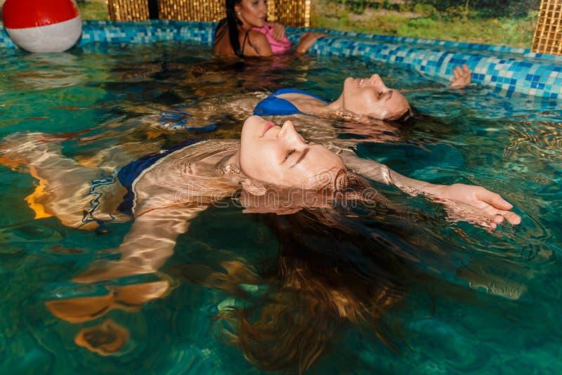 Trois amis féminins en piscine photo stock