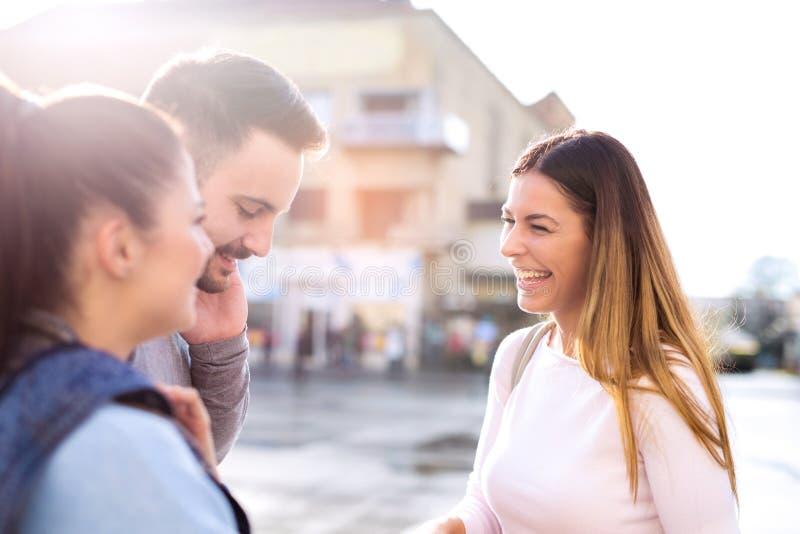Trois amis heureux parlant prenant une conversation sur la rue photographie stock libre de droits