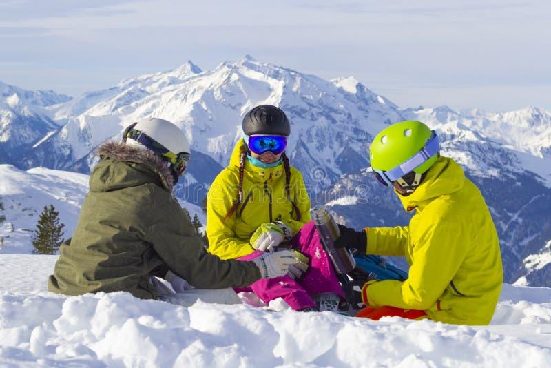 Trois amis heureux, snowboarders et skieurs, déjeunent sur la piste de ski par beau temps dans les montagnes images libres de droits