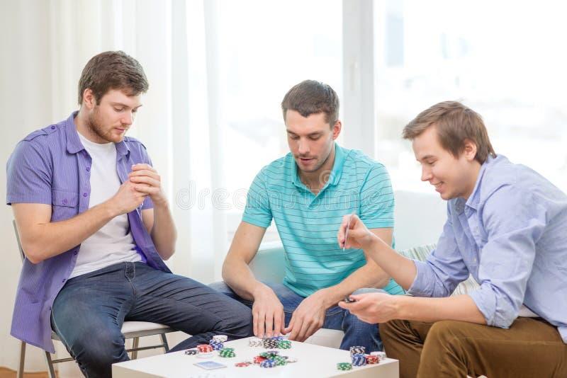 Trois amis masculins heureux jouant le tisonnier à la maison images stock