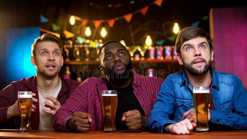 Trois amis masculins observant des dernières nouvelles sur le grand écran dans la barre, égalisant des loisirs photo libre de droits