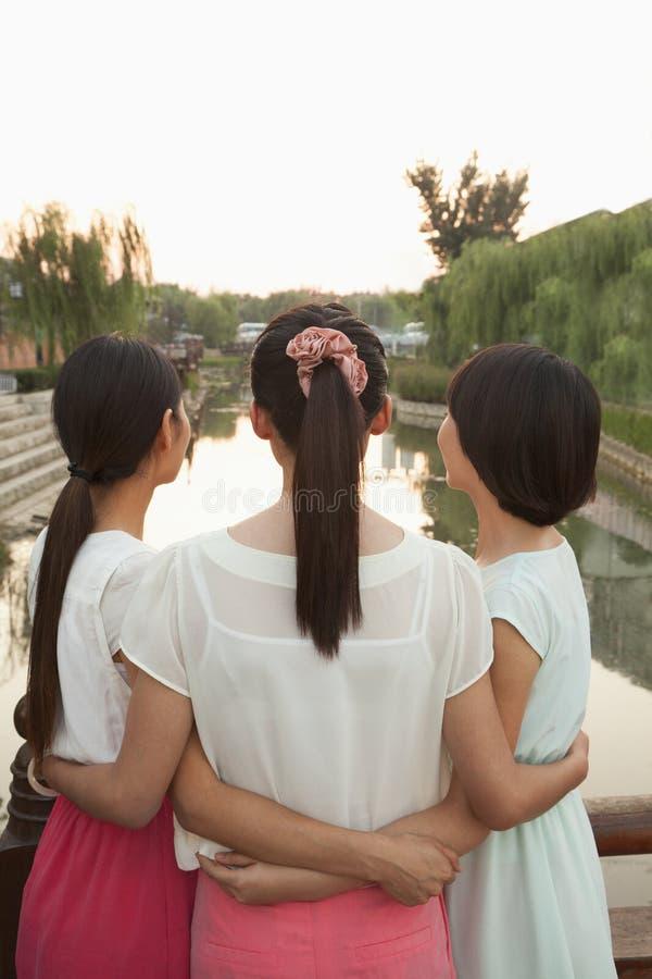Trois amis regardant la rivière photo stock