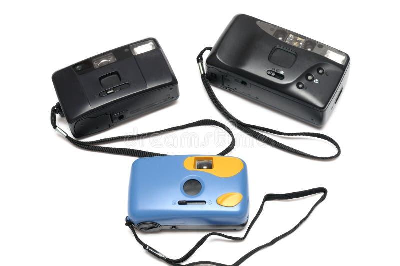 Trois appareils-photo de film avec les courroies de poignets noires Deux sont noir tandis que l'autre est bleu en couleurs photographie stock libre de droits