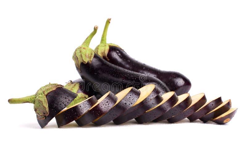 Trois aubergines, une aubergine est coupées en anneaux que les baisses de l'eau sur le fond blanc se ferment d'isolement photographie stock