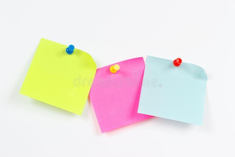 Trois autocollants multicolores sur la table des messages blanche photographie stock