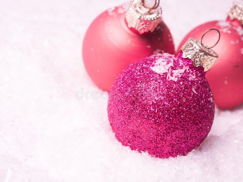 Trois babioles roses de Noël dans la neige photos libres de droits