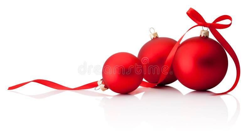 Trois babioles rouges de décoration de Noël avec l'arc de ruban d'isolement sur le fond blanc photos libres de droits