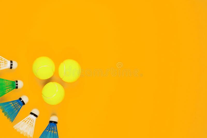 Trois balles de tennis à côté d'un groupe de volants, sur le fond jaune image libre de droits