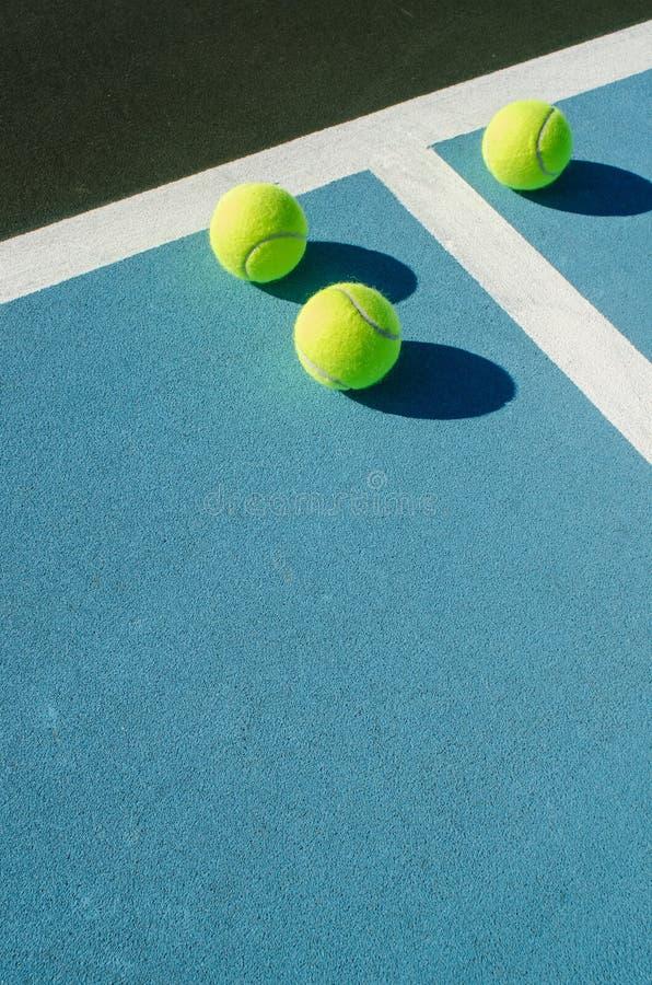 Trois balles de tennis sur le court de tennis bleu photographie stock