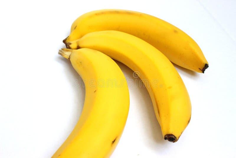 Trois bananes jaunes à un arrière-plan blanc photos libres de droits
