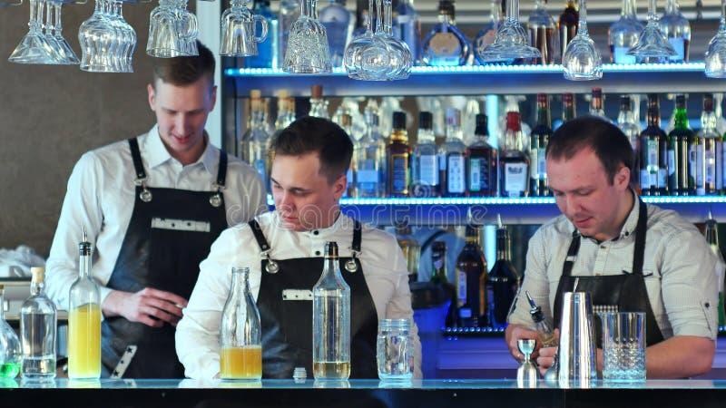 Trois barmans servant des cocktails et travaillant dans une barre chique image stock