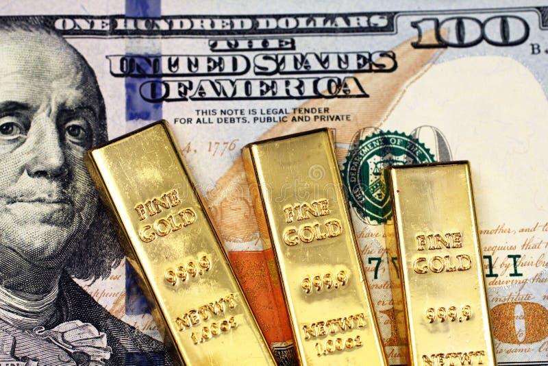 Trois barres d'or avec des cent billets d'un dollar américain photos libres de droits