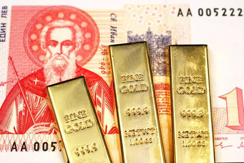 Trois barres d'or dans le macro avec une facture bulgare de lev photo stock