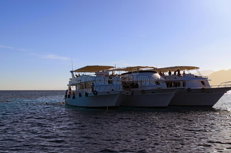 Trois bateaux de croisière amarrés près du récif sur la Mer Rouge calme photo libre de droits