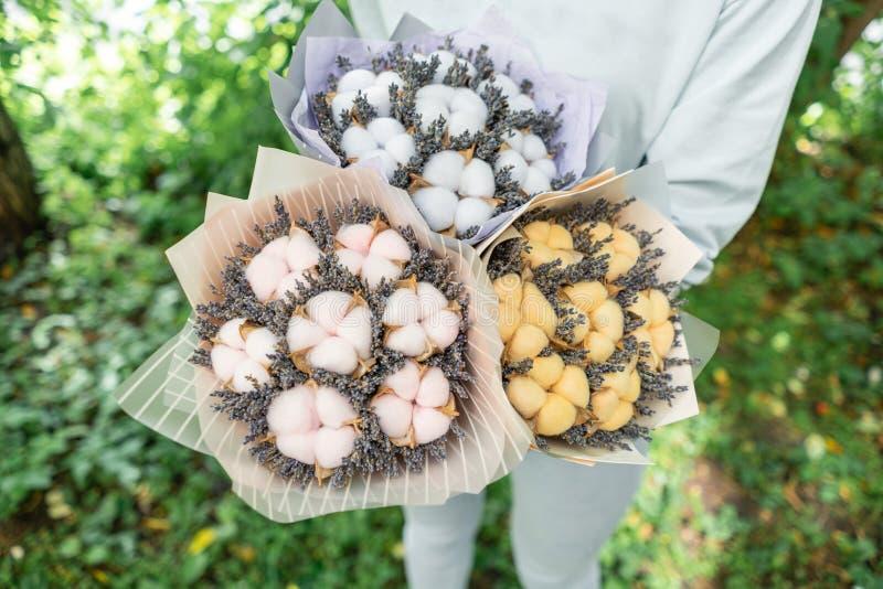 Trois beaux et lavande différente de bouquets avec du coton chez des mains de la femme r placé dans a image stock