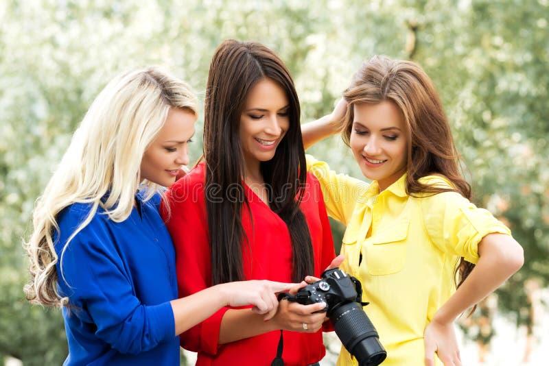 Trois belles femmes ayant un photosession dans le parc photo stock